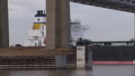 A towboat pushes a barge beneath a Mississippi River bridge.