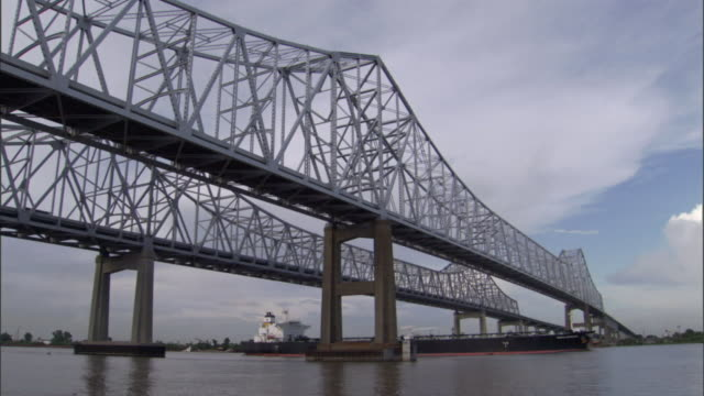 A towboat pushes a barge under a Mississippi River bridge.