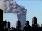 Towers billowing smoke building water supply tanks on rooftops in FG Helicopters fly by Shot from Manhattan rooftop