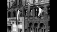 Town buildings businesses displaying Nazi swastika banners signs Saarland poster 'Wir wollen heim' countdown calendar for January 13th 1935...