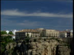 Town of Ronda built on cliff top zoom out to include ravine cliff face and foliage far below