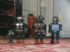 Toy robots walk across a carpet at a toy fair