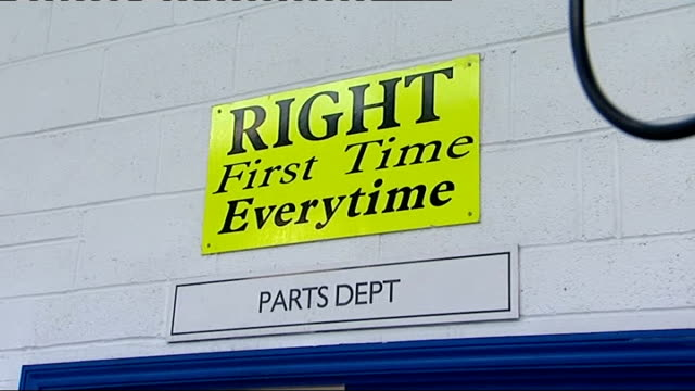 mechanic adjusts accelerator pedals 'The Customer is King' sign on workshop wall/ 'Right First Time' sign on wall/ Toyota owners in reception area of...