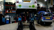 Toyota Prius car being raised up in garage as Steve Fowler shows reporter the underneath of car and explains possible braking problems SOT Close Shot...