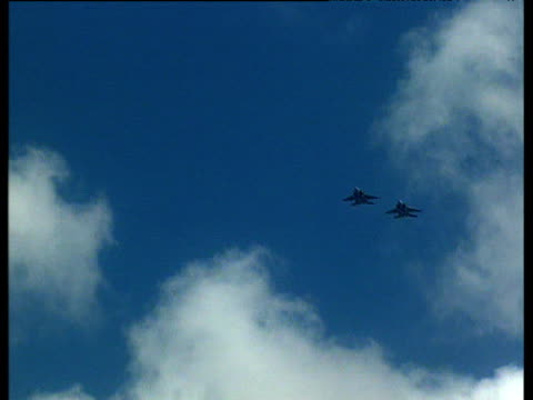 Track across blue and cloudy sky with three US military jets performing maneuvers during training session