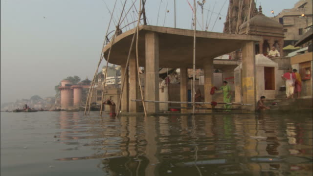 Track along Ganges past people bathing at ghats, Varanasi Available in HD.