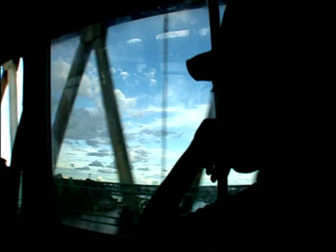 Track along lattice bridge above river as silhouetted passenger thoughtfully looks on Borneo