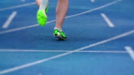Track and field athlete leaving start line in slow motion