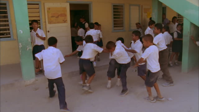 Track around schoolboys playing football with pink ball outside San Pedro Roman Catholic School, Belize Available in HD.