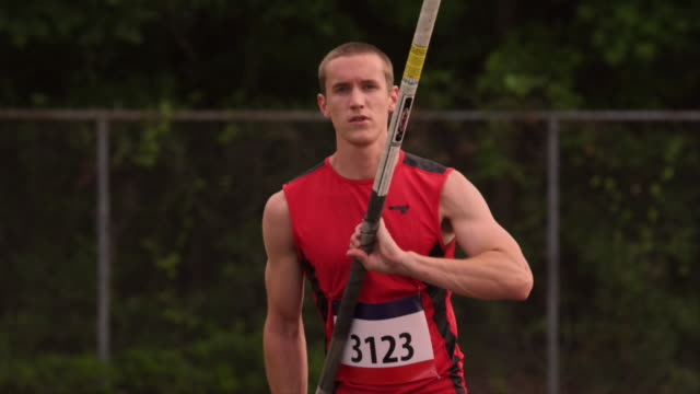A track athlete runs with a pole in his hands.