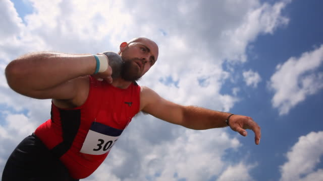 A track athlete spins around and throws a shot put ball into the air.