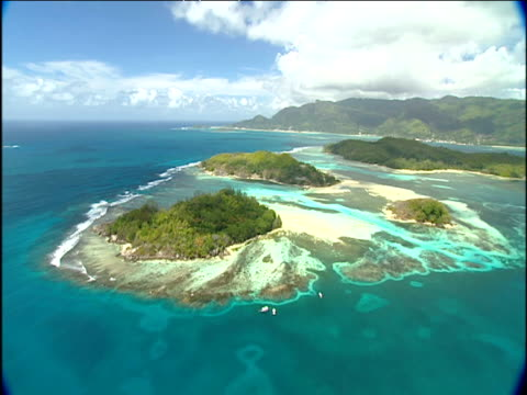 Track backwards over heavily vegetated island surrounded by turquoise ocean Seychelles