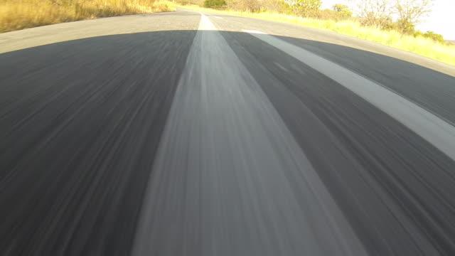 Track forward along asphalt road.