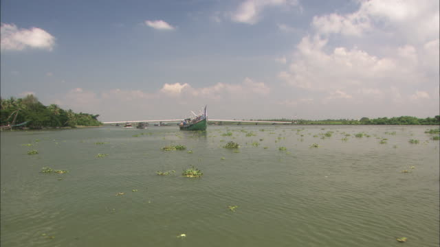 Track forward along Keralan backwaters passing fishing boat Available in HD.