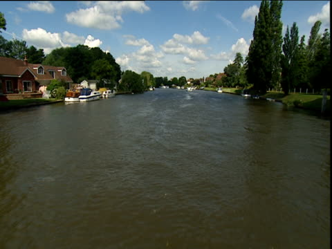 Track forward along River Thames at Staines past riverside houses and moored boats Surrey