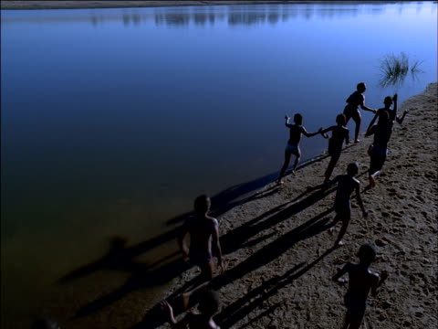 Track forward as group of boys wave arms as they run along beach by water's edge, South Africa