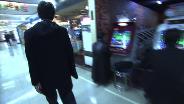 Track forward as teenager walks through shopping centre into an amusement arcade