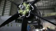 Track forward employees work above the propeller and open engine of a Bombardier Inc Q400 NextGen passenger aircraft undergoing maintenance at the...