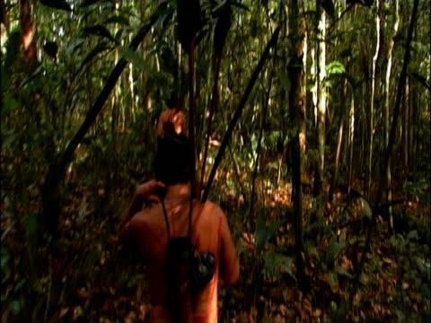 Track forward following two Sanema tribesmen through dense vegetation during hunt South Venezuelan Rainforest