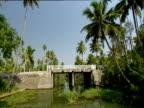 Track forward from boat along narrow river and under bridge India