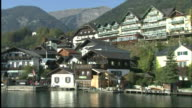 Track forward from boat approaching wharf on banks of Wolfgangsee overlooked by mountainside buildings