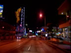 Track forward from car along strip past traffic and neon lit buildings Sunset Strip Los Angeles