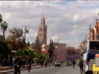 Track forward from car through streets with mosque tower in distance Marrakesh