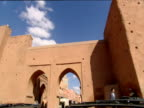 Track forward from car through windscreen as car turns and enters city through stone arch Marrakesh