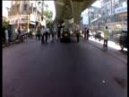 Track forward in car through busy traffic underneath flyover Bombay