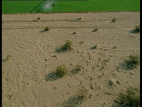 Track forward over desert to pivot irrigation system, Arizona