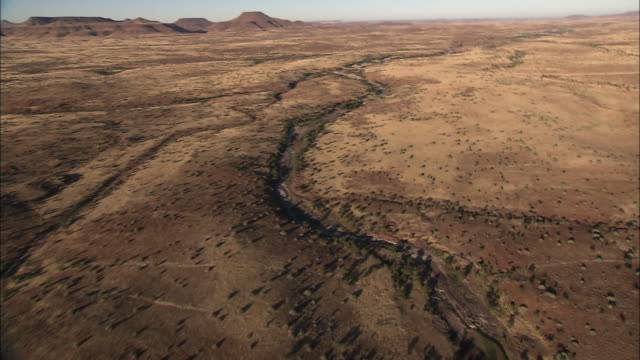 Track forward over river running through a canyon across the Kalahari Desert. Available in HD.