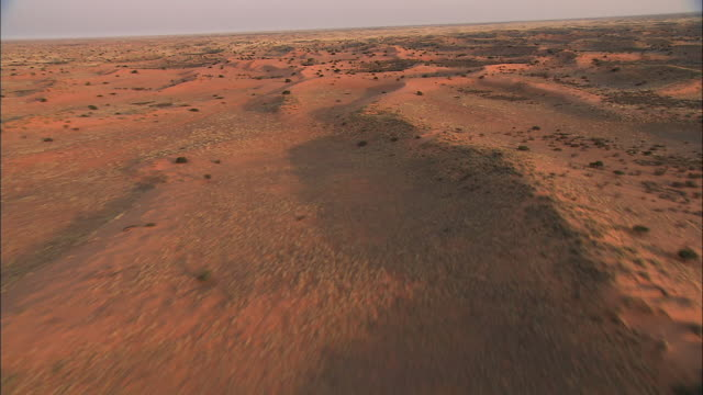 Track forward over winding ranges of desert hills cast shadows across the sandy landscape of the Kalahari Desert. Available in HD.