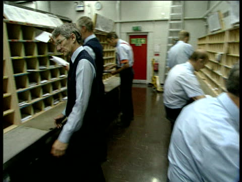 Track forward past Royal Mail postal workers sorting mail into pigeon holes