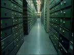 Track forward through small aisle in between towering green filing cabinets