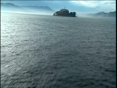 Track forwards across calm sea under dusky blue sky towards Alcatraz Island in distance. Beautiful shot