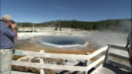 Track forwards across observation platform and zoom in to Crested Pool, Yellowstone National Park, Wyoming