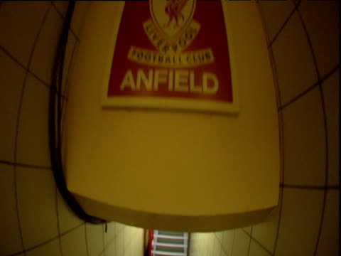 Track forwards along corridor under This is Anfield football club sign and out onto pitch Anfield stadium Liverpool