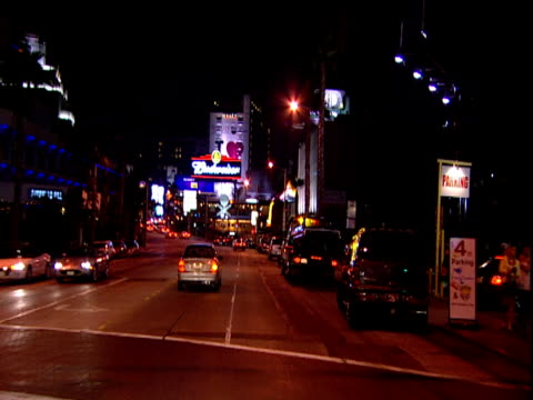 Track forwards from car along strip past neon lit buildings and traffic Sunset Strip Los Angeles