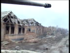 Track forwards from moving tank past demolished buildings Russian soldiers on tanks move through Grozny Feb 2000