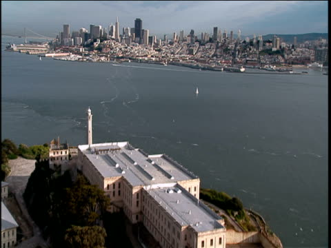 Track forwards over Alcatraz prison and surrounding sea towards skyline of San Francisco Bay