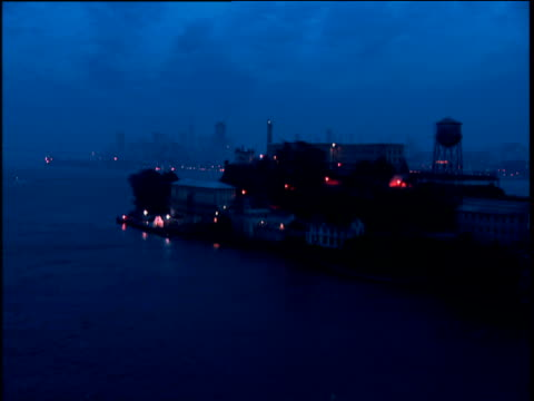 Track forwards past Alcatraz Island and surrounding water at night with lighthouse flashing. Lights from boats moored in San Francisco bay visible in background