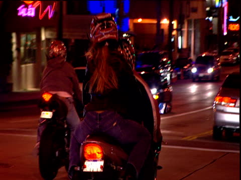 Track from car as motorcyclists speed off Sunset Strip Los Angeles
