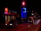 Track from car past busy traffic and neon lit Key Club Sunset Strip Los Angeles