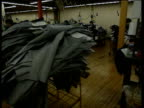 Track left across machinists sewing jeans in factory