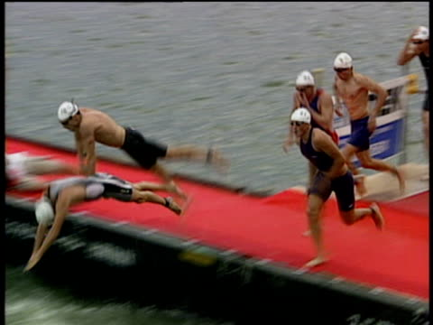Track left and zoom out slowly on Tri athletes diving into water during race