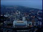 Track left around Millennium stadium with roof open illuminated in evening sky Cardiff