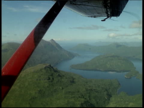 Track left from airplane over Kodiak Island Alaska wing and wing support in foreground