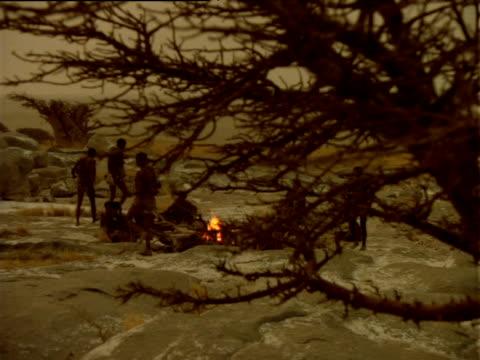 Track left from behind tree to reveal Basarwa tribesmen around camp fire, Botswana