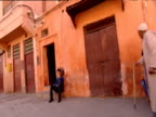 Track left from car past pedestrians in street Marrakesh