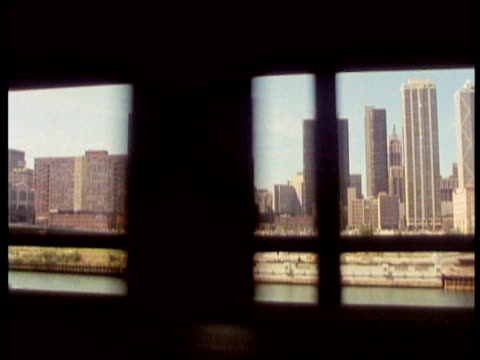Track left from L train (elevated) window past Chicago city financial district Chicago river in foreground